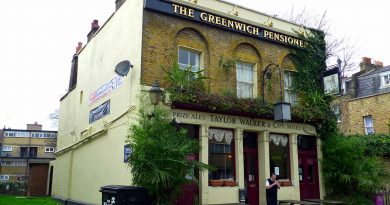 The exterior of The Pensioner Pub with green leafy plants around the windows and doors.