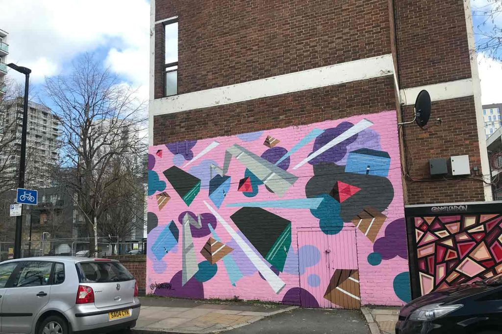 Painted on the side of a multiple story flat building. The Street art is pink, green, purple and blue.