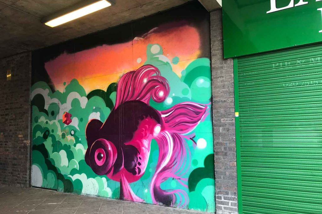 The pink fish street art is painted next to the green shutters of the EastEnders Pie n Mash Shop
