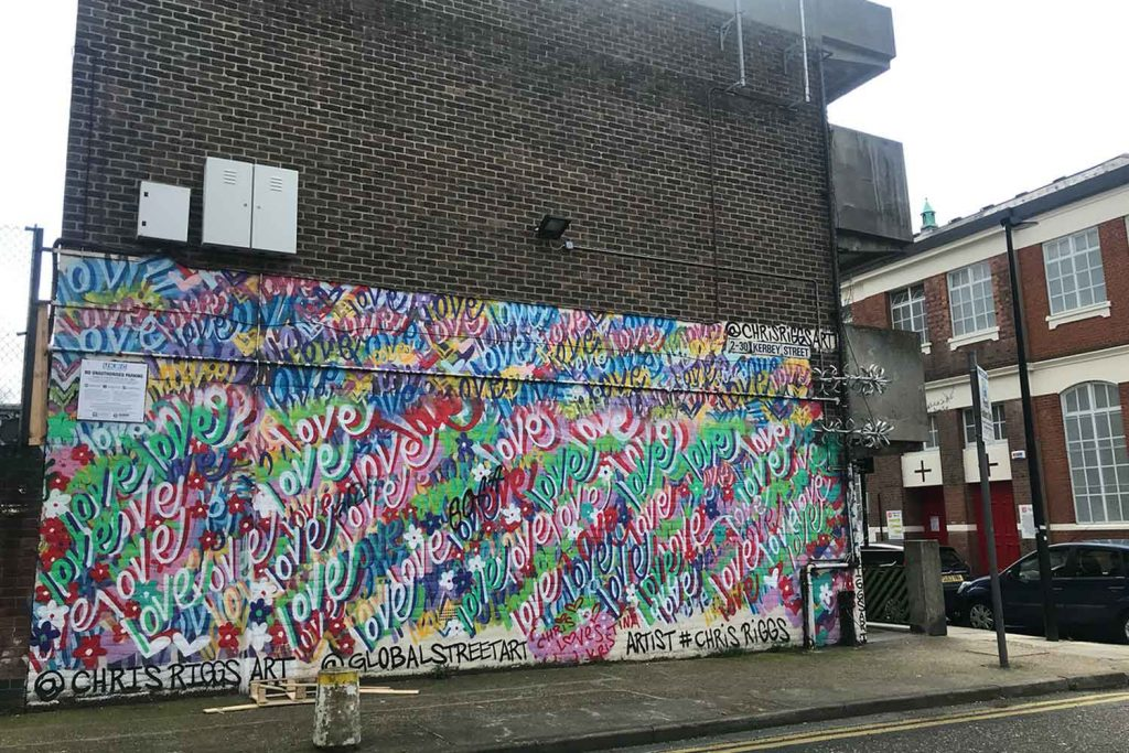 The love mural on Kerbey Street is painted on the side of multiple-story flat building.
