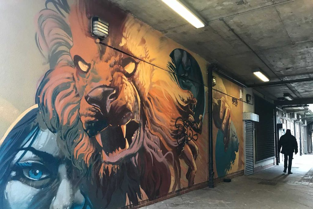The lion street art is painted in an alleyway.