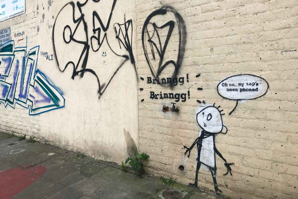 Painted on a cream brick wall, the Banksy street art is surrounded by graffiti