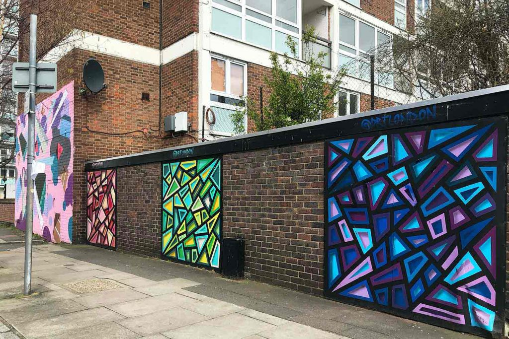 The red, green and blue stained-glass style street art by DRT is painted on a brown brick wall.