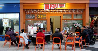 A group of people sat around round tables outside the orange The People Speak space on Aberfeldy Street