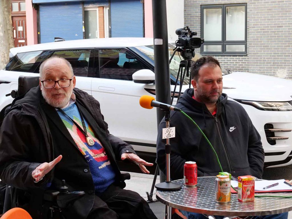 One man in a wheelchair and another sat next to him talk into a microphone at Aberfeldy Live Talkaoke