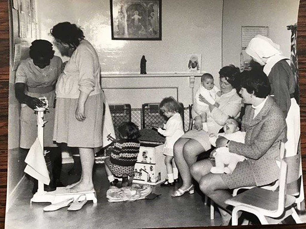 A nurse weighs a woman as women sit around her with children on on their knees at the anti-natel clinic in Poplar