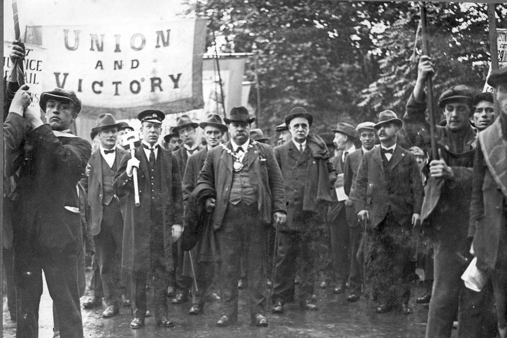 The start of the march. Charlie Sumner stands wearing the chain-of-office, he was Deputy Mayor