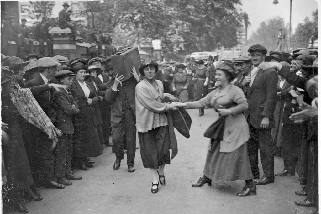 Women steps out of crowd and grabs Minnie Lansbury's hand