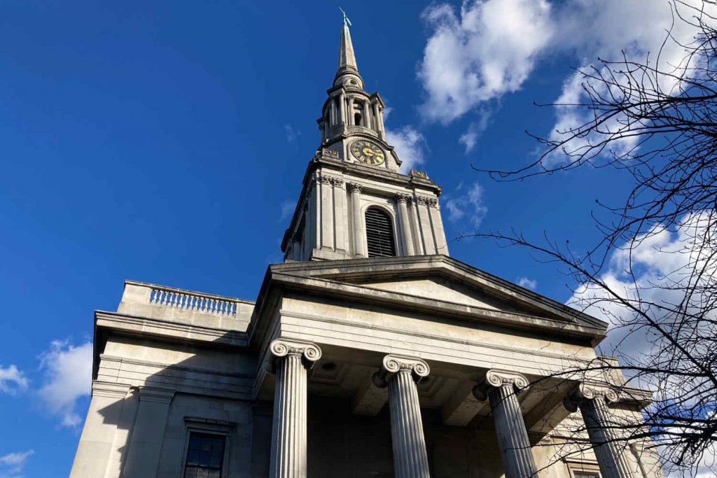 All Saints, a white stone church with Greek pillars
