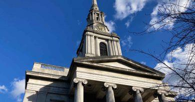 All Saints, a white stone church with Greek pillars.
